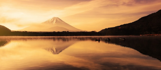 Mount fujisan with fishermen on boats and mist at shoji lake at sunrise in yamanashi, japan.