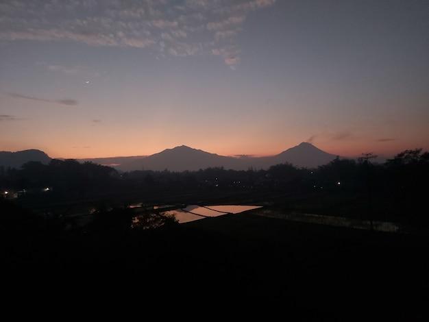 朝日が昇るメラピ山とメルバブ山