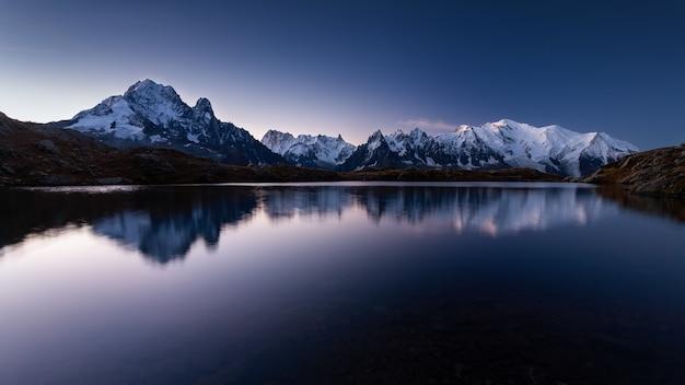 Гора монблан покрыта снегом, отражаясь в воде вечером в шамони, франция