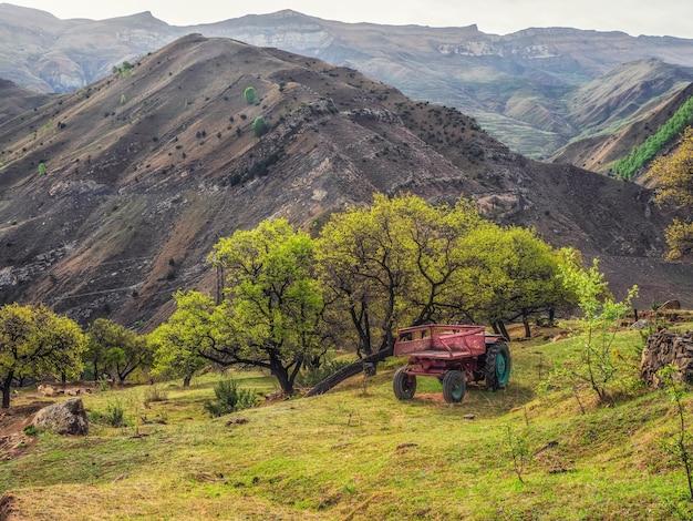山岳農業。山々を背景に緑の木々の下に古いトラクターが立っています。ダゲスタン。