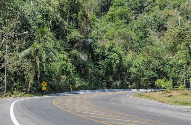 滑りやすい舗装警告標識のある山のアスファルト道路