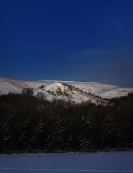 Гора ночью освещена светом полной луны. фото сделано зимой в россии.