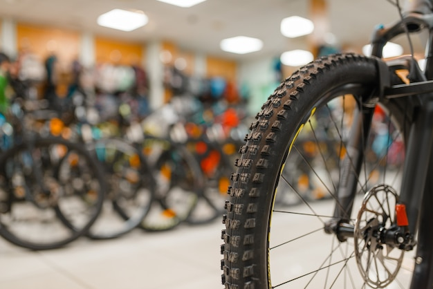 Mountain bicycle in sports shop, focus on front wheel