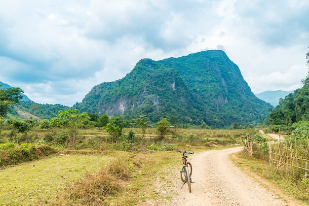 ヴァンヴィエン周辺の風光明媚な風景の中の未舗装の道路でのマウンテンバイク