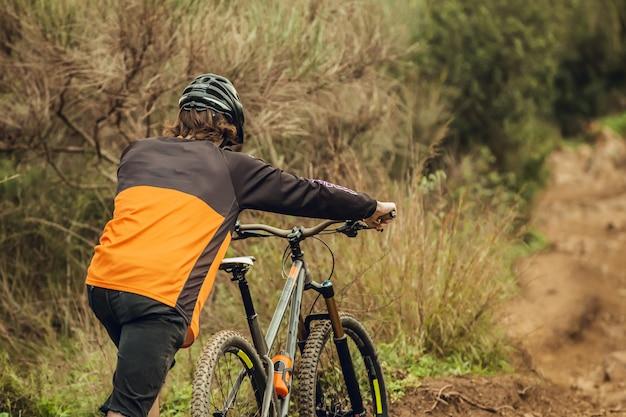 Mountain bike rider climbing up mountain trail