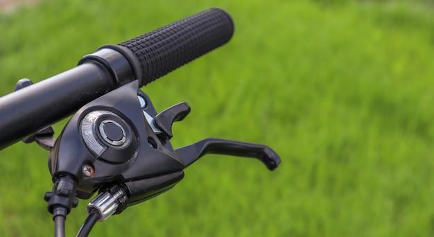 緑の芝生の背景にマウンテンバイクのステアリングホイール Premium写真