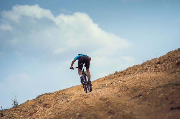 マウンテンバイカーのサイクリング、トレーニング、急な登り。