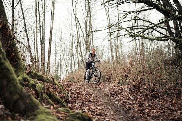 Motociclista della montagna che guida la bici sulla traccia della foresta in autunno