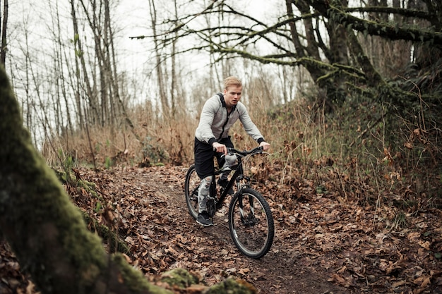 森林のトレイルでスポーツバイクに乗るマウンテンバイカー