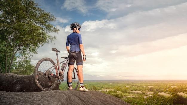 Горный велосипедист стоит с парой горных велосипедов mtb на скале, чтобы посмотреть на горы природы. спортсмен на горных велосипедах смотрит на дикую природу на горе. экстремальный спорт и горный велосипед, концепция скоростного спуска на горных велосипедах