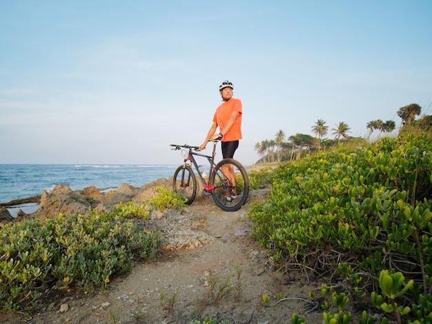 산악 자전거는 자전거로 바다 해안에 서 있습니다.