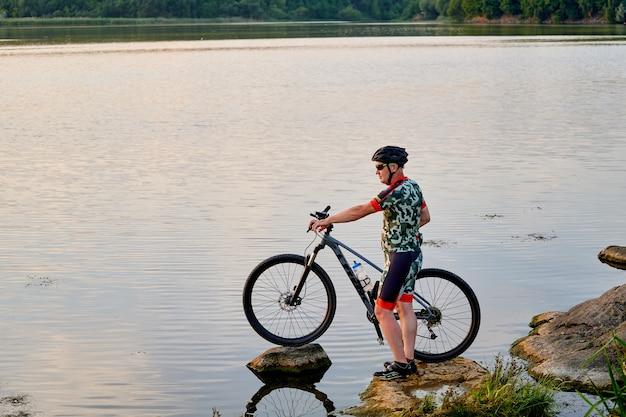 湖の岩の上で自転車を持っているマウンテンバイカー。冒険への動機とインスピレーション。エクストリームスポーツのコンセプト。