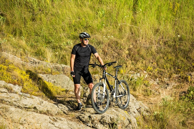 Mountain biker with a bicycle on a rock. motivation and inspiration for adventure.