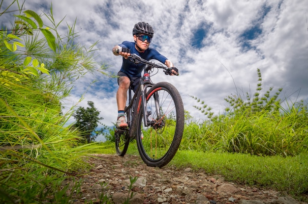 Mountain bikers ride mtb, mountain bike downhill to the extreme.  asian man rides mtb, mountain bike in the wild to extremes. extreme sport and mtb, mountain bike concept.