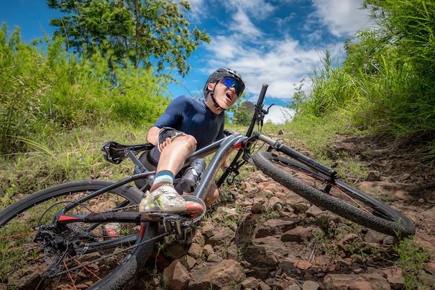 산악 자전거는 mtb를 타고, 산악 자전거는 내리막에서 사고를 당합니다. 아시아 남자는 mtb를 타고, 산악 자전거는 야생에서 내리막길에서 사고를 당했습니다. 자전거 내리막 사고 개념입니다.