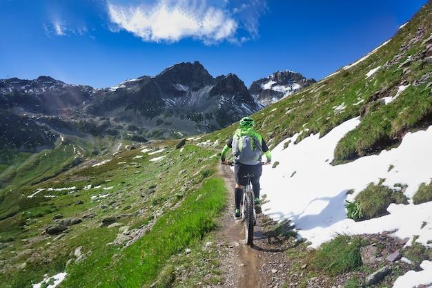Катание на горных велосипедах по небольшой узкой горной тропе