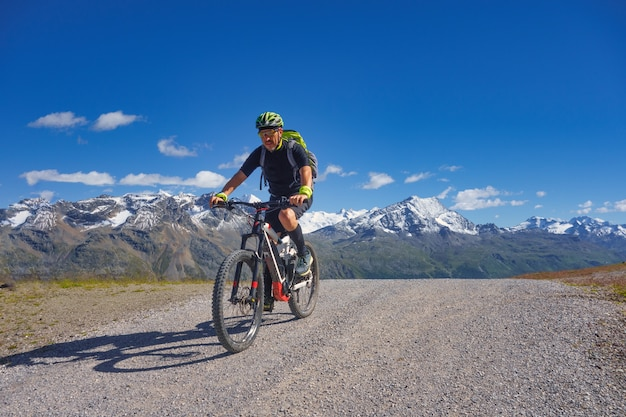未舗装の道路の高山でのマウンテンバイク