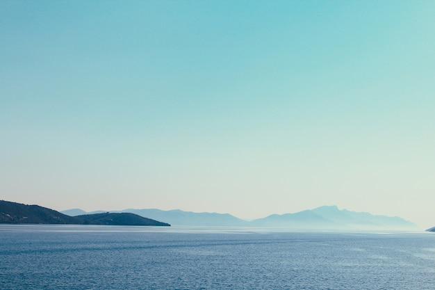 Горная цепь через побережье эгейского моря в греции. пейзаж, который сочетает в себе горы, море, голубое небо и дневной свет. небесно-голубой успокаивающий цвет. атмосфера медитации.
