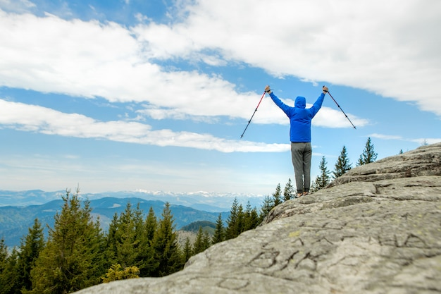 Mountain climber is high in the mountains against the sky, celebrating the victory, raising his hands up.
