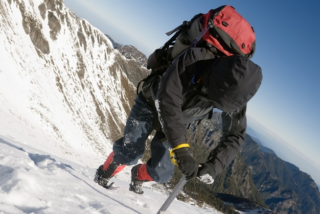 登山家は冬にピッケルを使って雪の氷の斜面を歩きます。