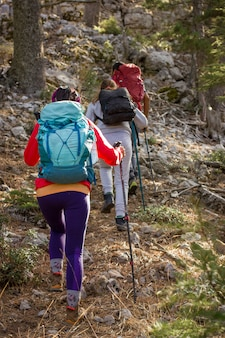 Mountain climbing. three people go uphill with trekking poles and backpacks.