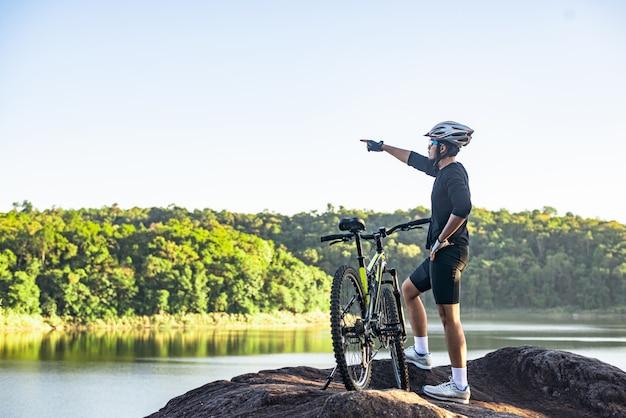 マウンテンサイクリストは自転車で山の頂上に立って、指を前に向けます。