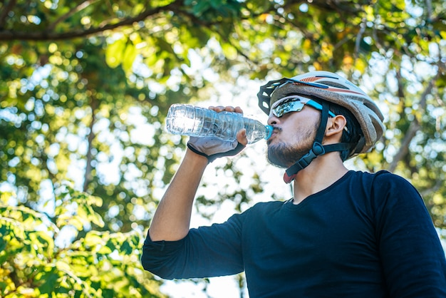 Mountain cyclists stand on the top of the mountain and drink a bottle of water.