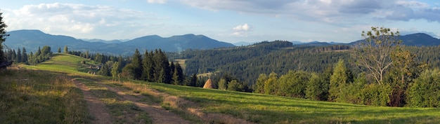 Mountain evening panorama view with earth road, haystackes and country estate (slavske village outskirts, carpathian mts, ukraine). nine shots composite picture.