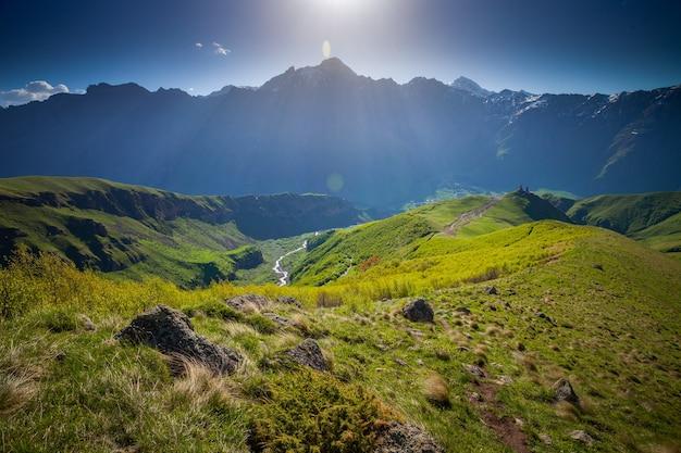 太陽の光が明るく輝く青い澄んだ空を背景にした山の緑の丘。自然の景観。旅行の背景。ツミンダサメバ。ジョージア州のカズベック山近くの聖三位一体教会。ヨーロッパ