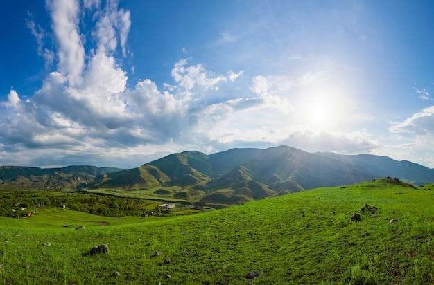 太陽が明るく輝く青い曇り空を背景にした山の緑の丘。自然の風景。旅行の背景。休日、ハイキング、スポーツ、レクリエーション。美の世界を探る:ジョージア州コーカサス山脈