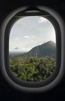 Горы, зеленый тропический лес и вид на небо из окна самолета. концепция бронирования go travel