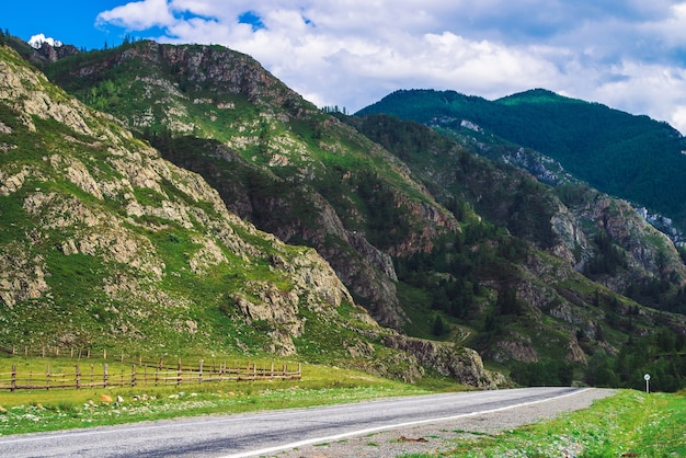 Mountain highway across pass in sunlight. asphalt road near foot of giant mountains.
