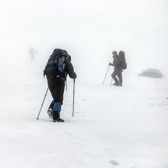 Группа горных походов с рюкзаками и треккинговыми палками, совершающая тяжелое восхождение в зимнюю снежную бурю