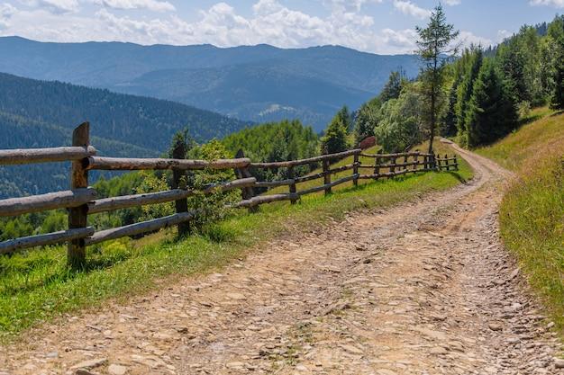 Горные холмы чистая природа сельский пейзаж. забор из деревянных бревен.