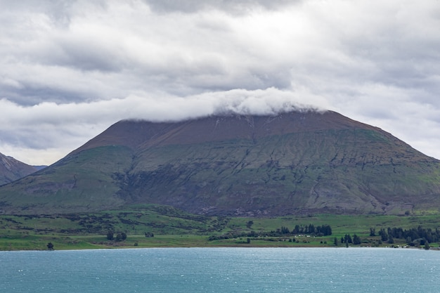 Гора в шапке облаков район квинстауна озеро вакатипу новая зеландия