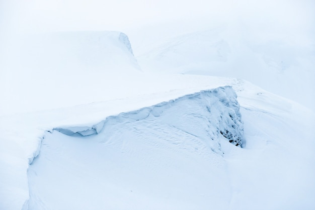 霧と青い雪の山。冬の風景