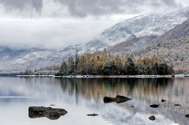 Mountain lake froliha, pine tree and stones with snow at mirror lake