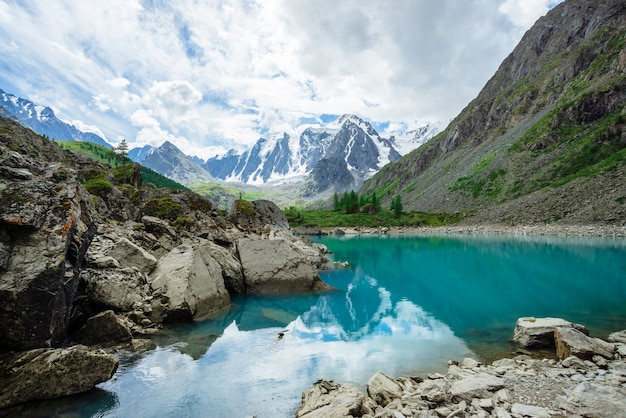 Mountain lake is surrounded by large stones and boulders on front of giant beautiful glacier.