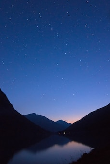 Mountain lake in the mountains in the background of the starry night sky
