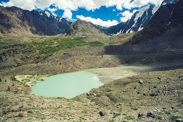 Mountain lake in shape of comet near huge rocky mountains. amazing snowy mountain ridges. wonderful giant glacier under cloudy blue sky. atmospheric cosmic landscape of majestic nature of highlands.