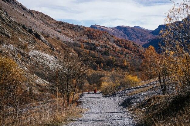 人々が歩いている晴れた秋の日の北イタリアの山の風景