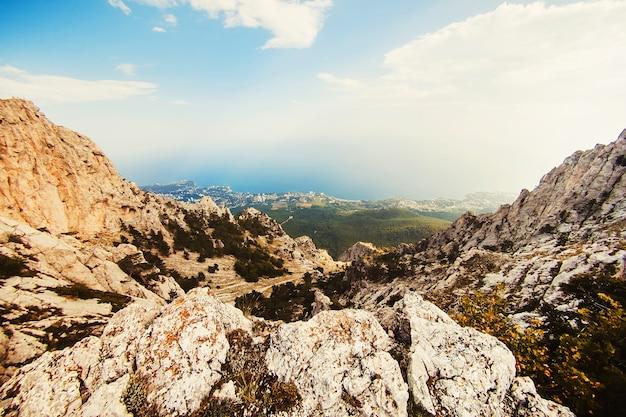 太陽の下で山の風景。強大な山。山から海への眺め。ロッキー山脈と青い空。山に掛かる雲。