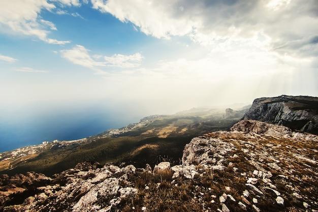 太陽の下で山の風景。強大な山。山から海への眺め。ロッキー山脈と青い空。