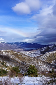 Горный пейзаж панорамный со снегом и радугой на горизонте. ла моркуера.