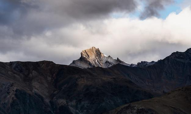 Mountain landscape, sunlight on mountain peak with overcast sky