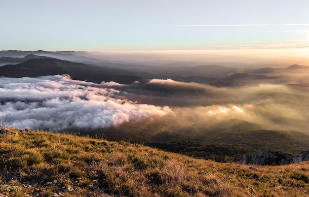 Mountain landscape at sunset with low clouds