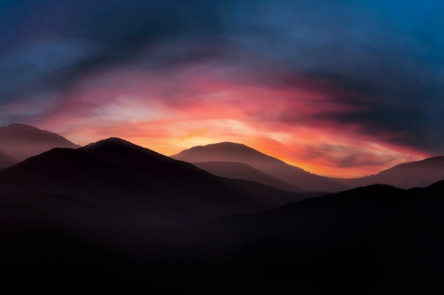 Mountain landscape with dramatic cloudy sunrise sky and morning fog