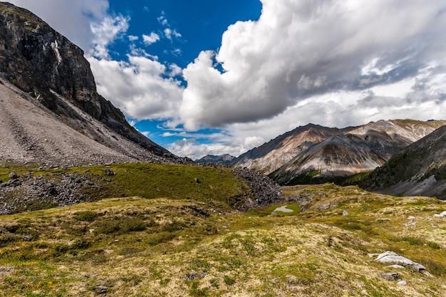Горный пейзаж с высокими горами и низкими белыми облаками