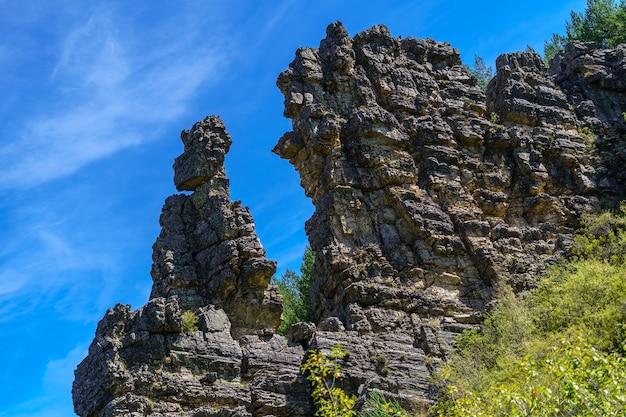 Горный пейзаж с высокими скальными образованиями в равновесии, деревьями и горной дорогой. сомосьерра, испания.