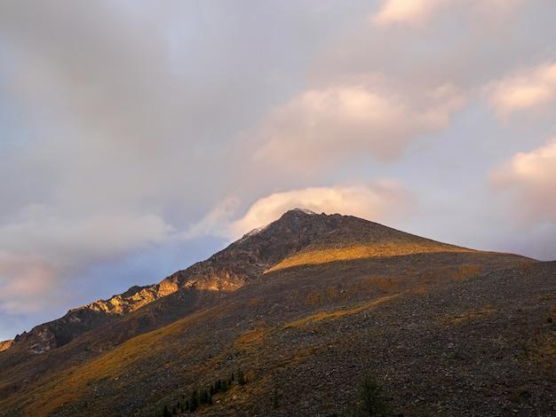 美しい黄金の夕日の岩と山の風景。鋭い岩と緑の森と岩山の壁の自然の背景。高い岩山のあるカラフルな夜明けの背景。